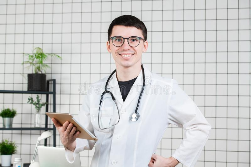 Smiling handsome young male doctor using tablet computer. Technologies in medicine concept stock photos