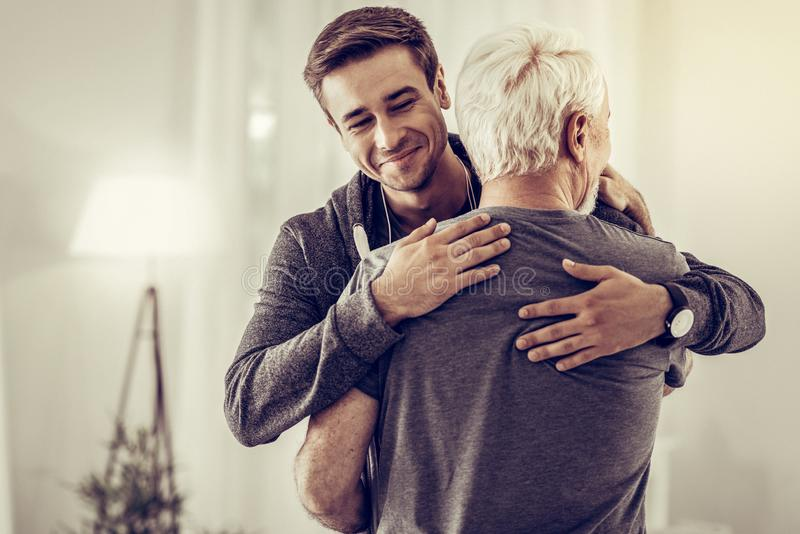 Smiling handsome young man embracing grey-haired dad cheering him up royalty free stock photo