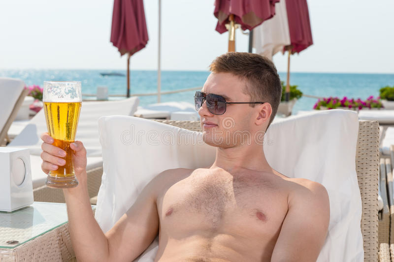 Smiling handsome young man enjoying a beer. Smiling handsome young man wearing sunglasses lying on a recliner chair at the seaside enjoying a beer on his summer royalty free stock photography