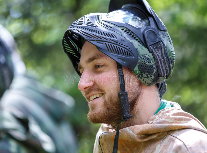 Smiling handsome young man in opened paintball mask stock images