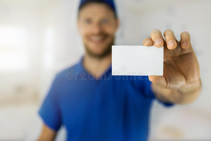 Smiling handyman in blue uniform showing blank business card stock images