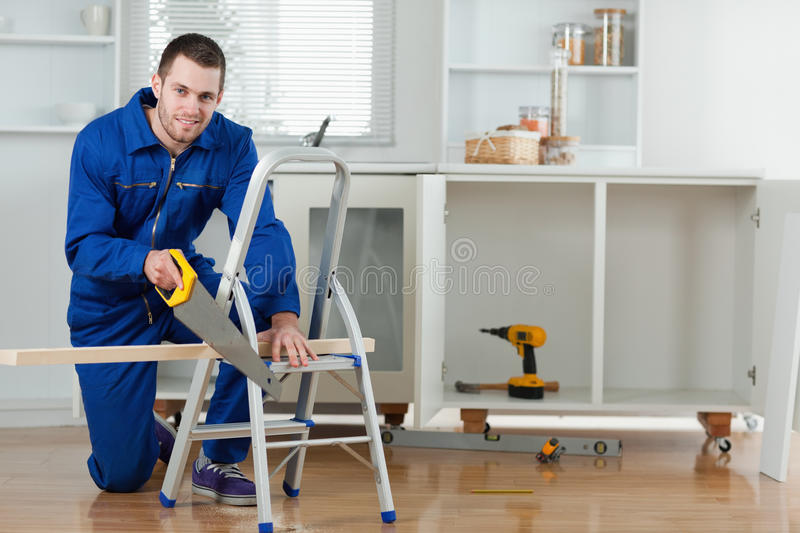 Smiling Handyman Cutting A Wooden Board Royalty Free Stock Image