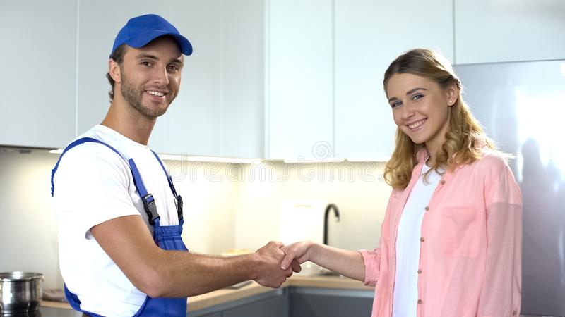 Smiling handyman and female client shaking hands and smiling to camera, service royalty free stock photo