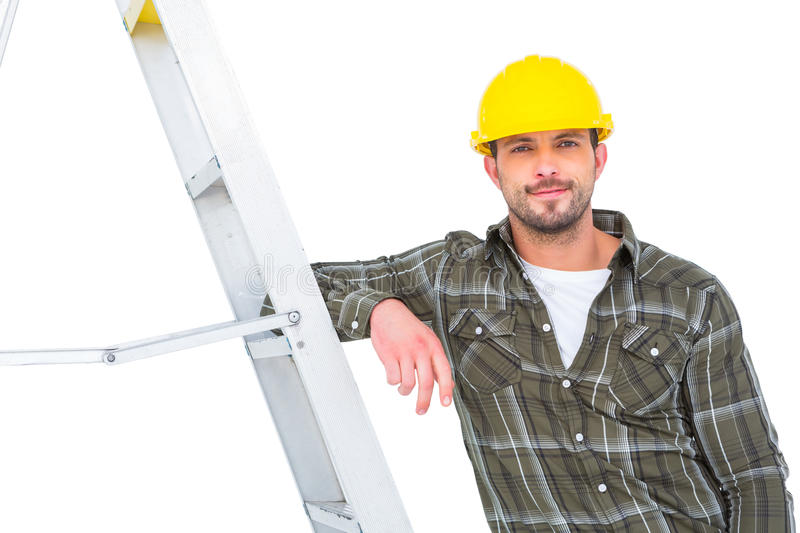 Smiling handyman in overalls leaning on ladder stock image