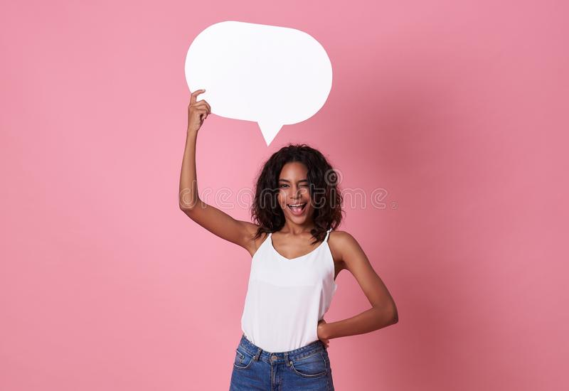 Smiling happy african woman holding blank speech bubble and looking at the camera on pink  background royalty free stock photo