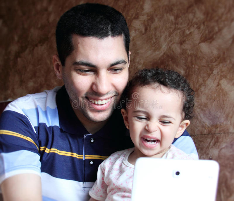 Smiling happy arab egyptian father with daughter taking selfie. Photo of smiling arabian father with his little daughter taking selfie with tablet and feeling royalty free stock photography