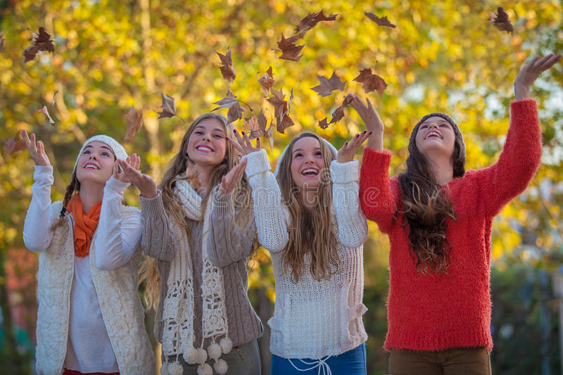 Smiling happy autumn teens leaves. Happy teens catching leaves and smiling royalty free stock images