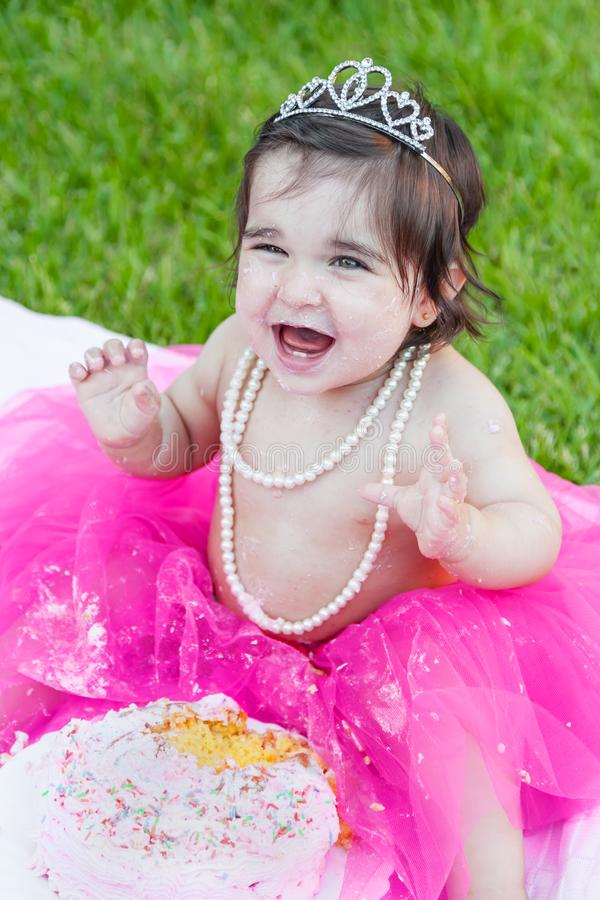 Baby toddler girl in first birthday anniversary party. Smiling happy baby toddler girl first birthday anniversary party. Ecstatic and laughing, raised hands stock photography