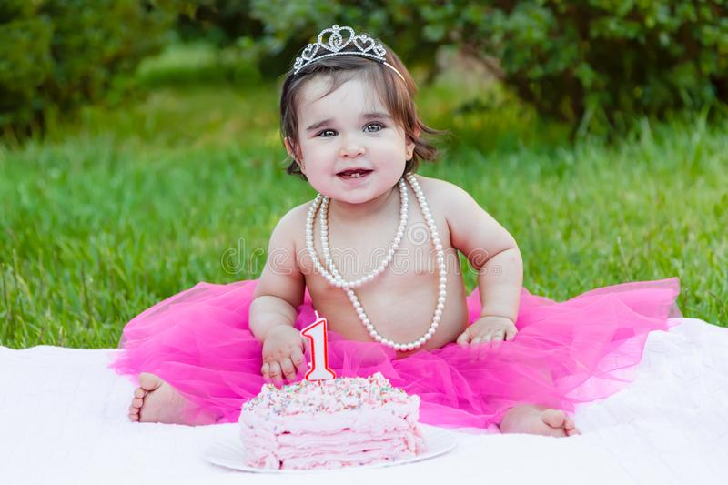 Baby toddler girl in first birthday anniversary party. Smiling happy baby toddler girl in first birthday party with pink cake outdoor. Dressed with princess stock photography