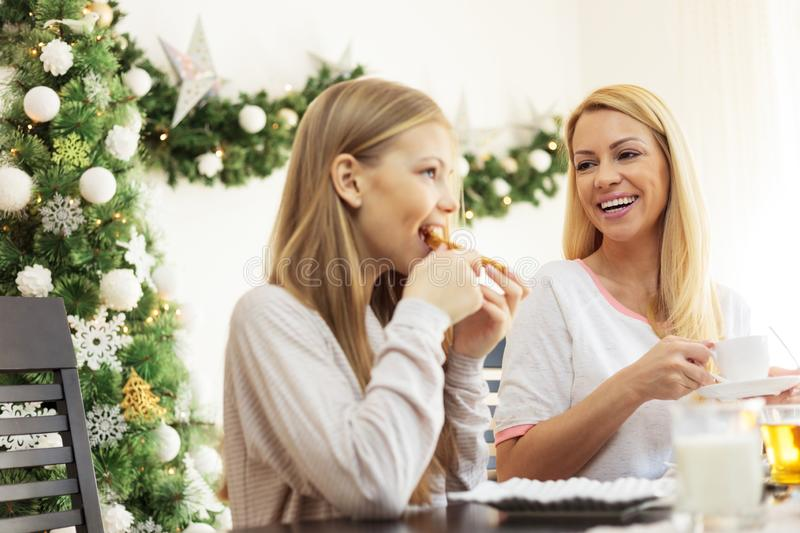 Smiling happy blond haired single mother and teenage daughter enjoying breakfast on Christmas day. Young woman drinking coffee royalty free stock photo