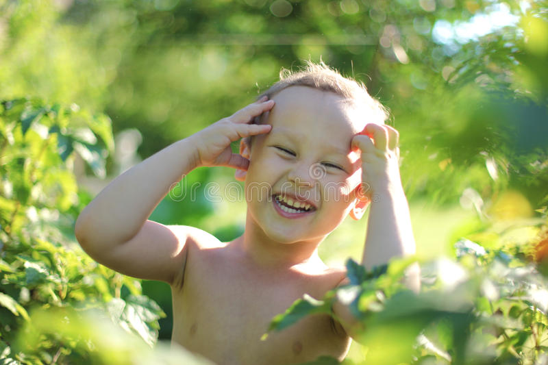 Smiling happy boy outdoors. Soft focus glass royalty free stock images