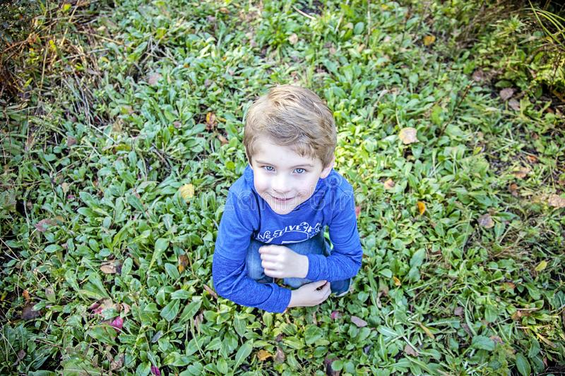Smiling happy boy sitting in grass outside stock photos