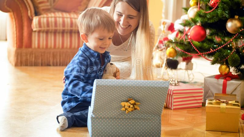 Portrait of smiling happy boy sitting under Christmas tree and opening gift boxes royalty free stock image
