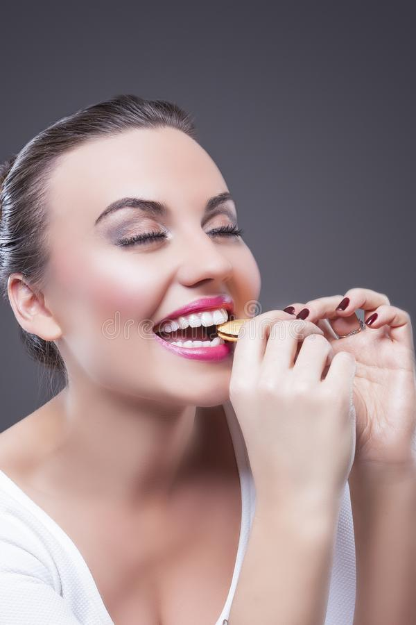 Smiling Happy Brunette Girl Biting Round Cookie stock photos
