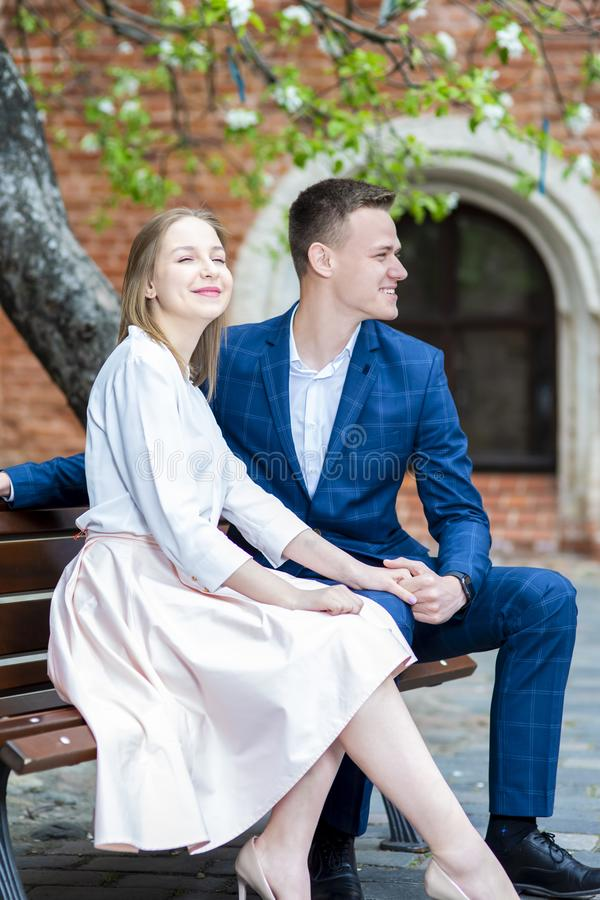 Smiling Happy Caucasian Couple Sitting on Bench in Cosy Yard Outdoors. Vertical Shot stock photo
