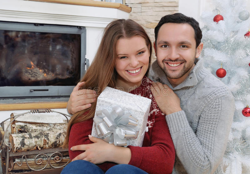 Smiling and happy couple with gifts for Christmas sitting near f royalty free stock photos