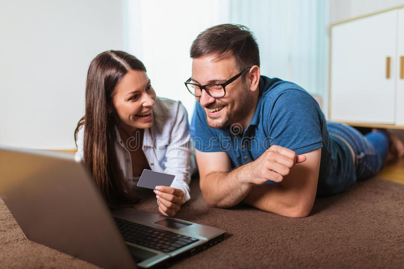 Happy couple with laptop and credit or bank card shopping online at home. Smiling happy couple with laptop and credit or bank card shopping online at home royalty free stock photography