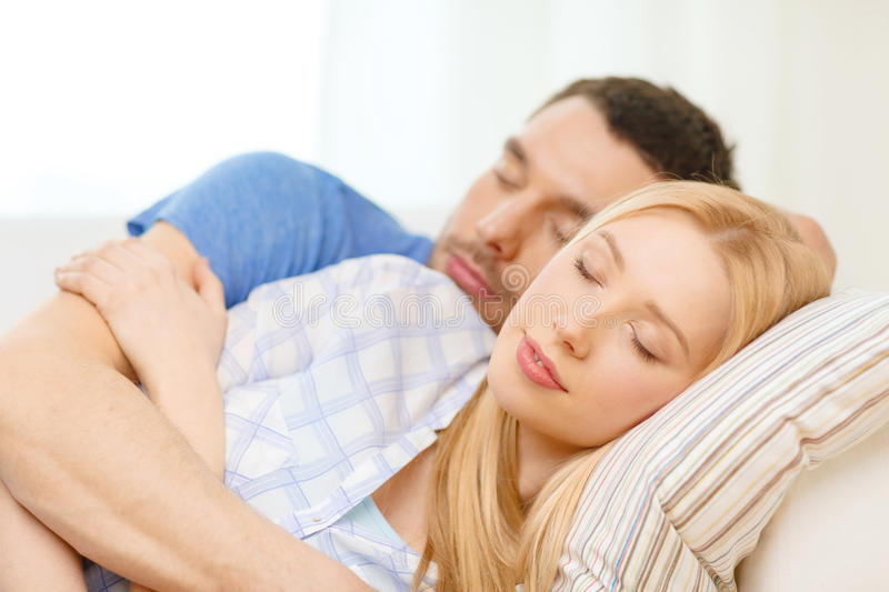 Smiling happy couple sleeping at home stock photography