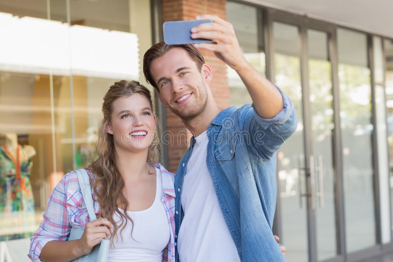 A smiling happy couple taking selfies stock photography