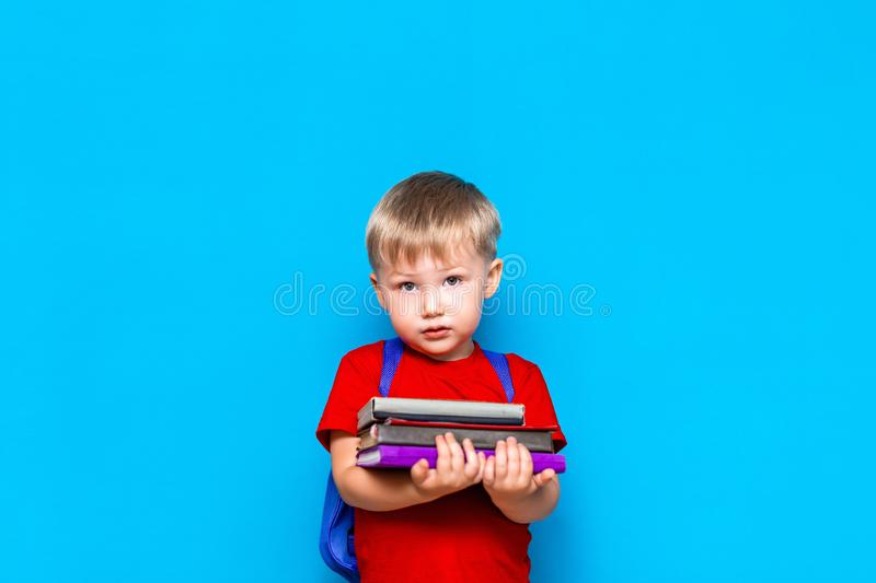 Smiling happy cute clever boy with backpack. Child with a pile of books in his hands. blue background. Ready for school. Back to. School royalty free stock images