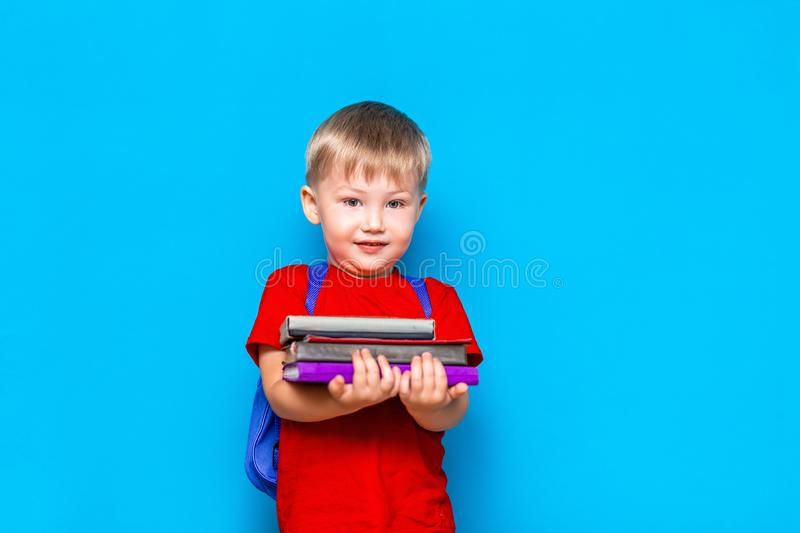 Smiling happy cute clever boy with backpack. Child with a pile of books in his hands. blue background. Ready for school. Back to. School stock photos