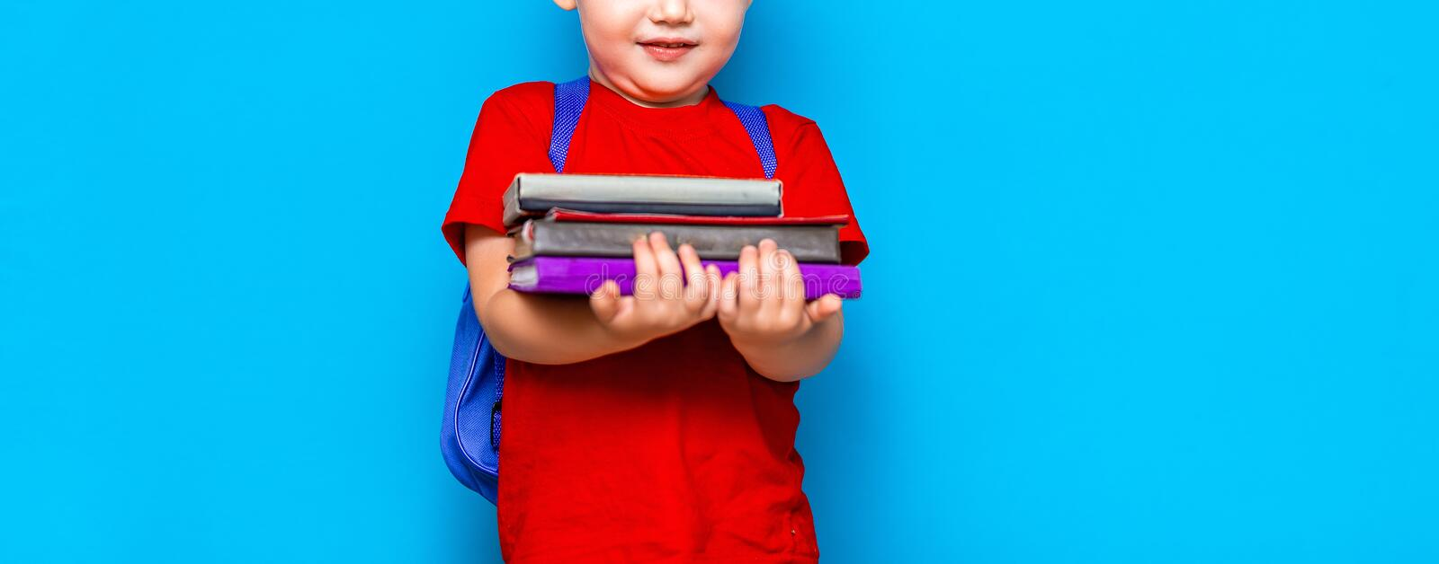 Smiling happy cute clever boy with backpack. Child with a pile of books in his hands. blue background. Ready for school. Back to. School royalty free stock photography