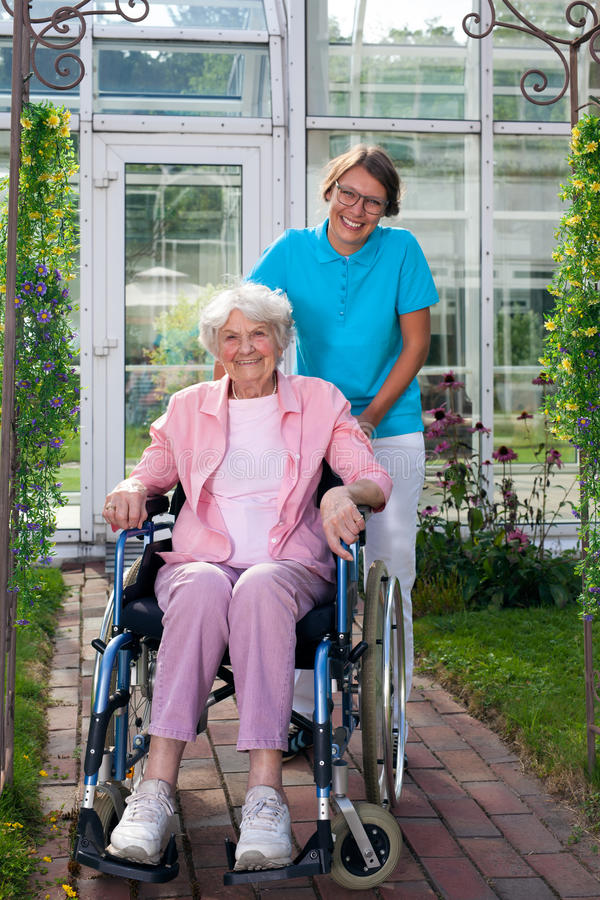 Smiling happy elderly lady in a wheelchair. royalty free stock image