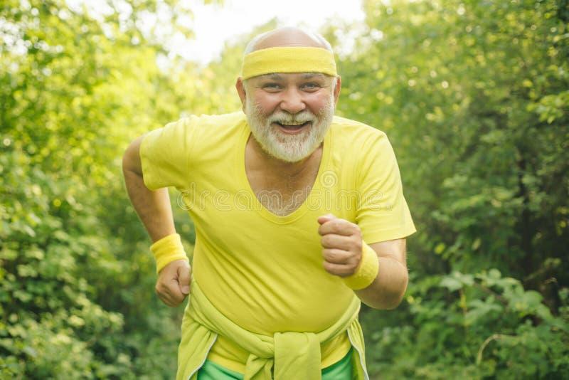 Smiling happy elderly man running. Senior man is doing sport outdoors. Senior man workout in rehabilitation center. The royalty free stock photo