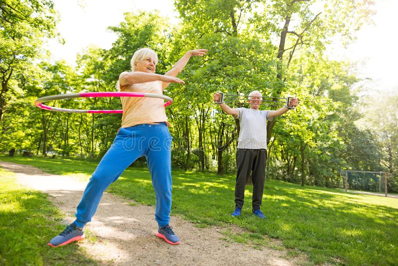 Senior Couple Exercising In Park. Smiling happy elderly seniors couple stock image