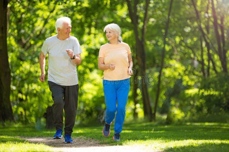 Senior couple running in park royalty free stock photos