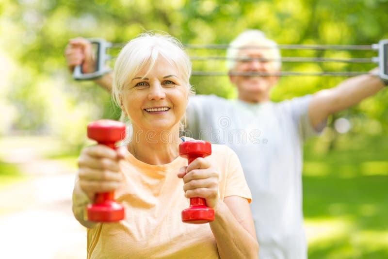 Senior Couple Exercising In Park. Smiling happy elderly seniors couple royalty free stock image