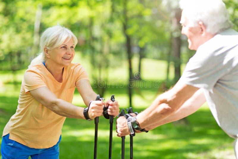 Senior couple nordic walking in park. Smiling happy elderly seniors couple royalty free stock photo