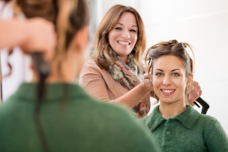 Smiling happy faces of a hairstylist and client royalty free stock photography