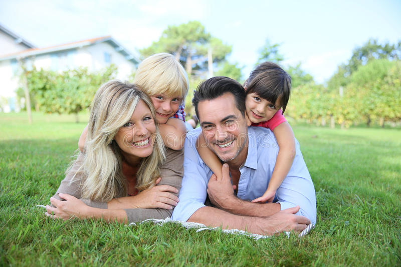 Smiling happy family of four lying in grass. Family of four laying on grass in front of house royalty free stock images