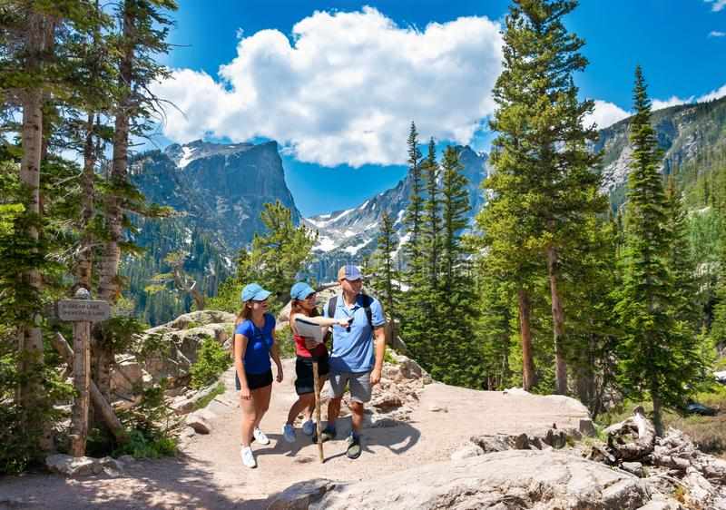 Smiling happy family relaxing on the hiking trail. People enjoying time together in the mountains on  Emerald trail. Estes Park, Rocky Mountains National Park royalty free stock photography