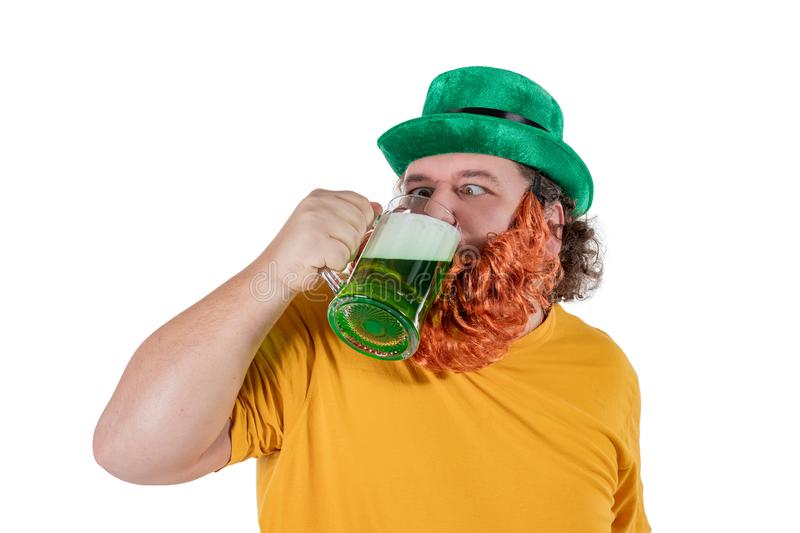 A smiling happy fat man in a leprechaun hat with green beer at studio. He celebrates St. Patrick royalty free stock image
