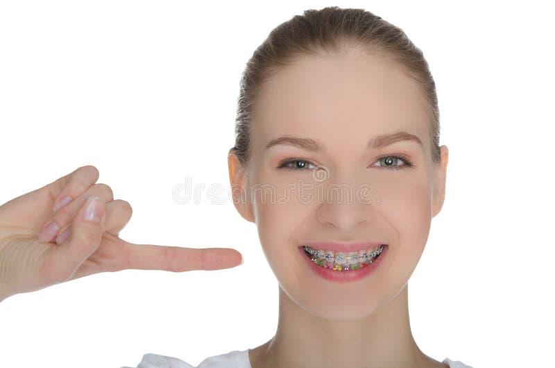 Smiling happy girl indicates braces on teeth. Isolated on white stock image