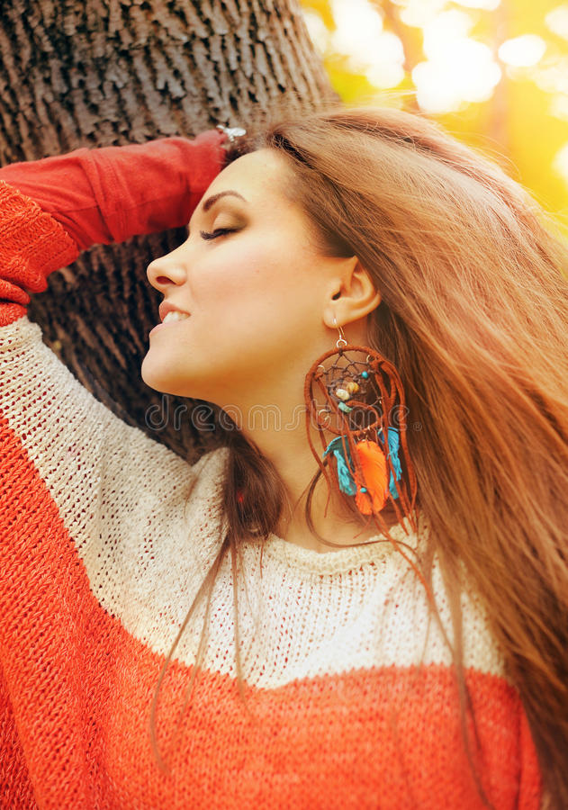 Smiling happy girl profile beauty portrait, fashion boho chic style dreamcatcher earrings, autumn outdoor. Soft vintfge colors stock photos