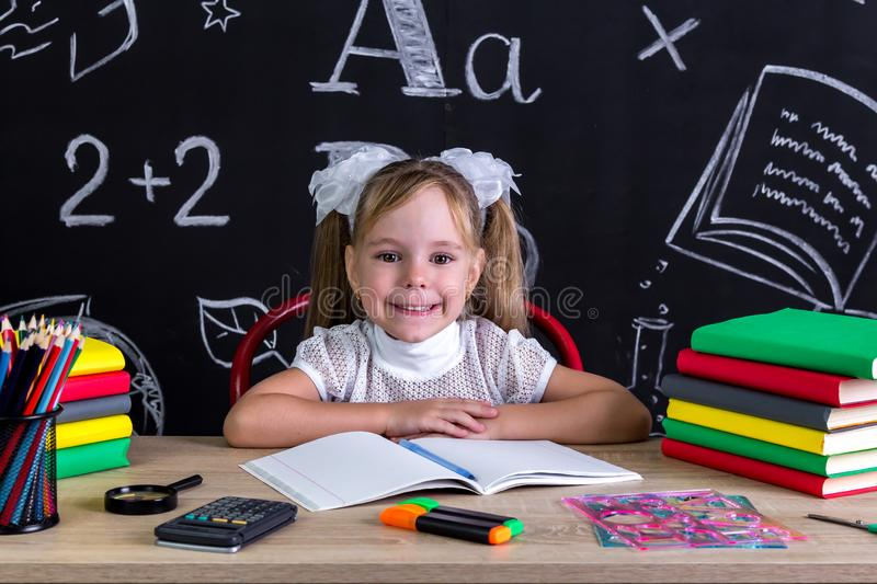 Smiling and happy girl sitting at the desk with books, school supplies stock photos