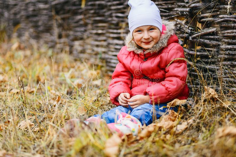 Smiling girl sitting on the dry autumn grass and looking at the camera royalty free stock image