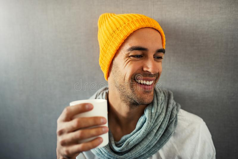 Smiling and happy handsome young man drinking coffee, tea, water, with white mug. stock images