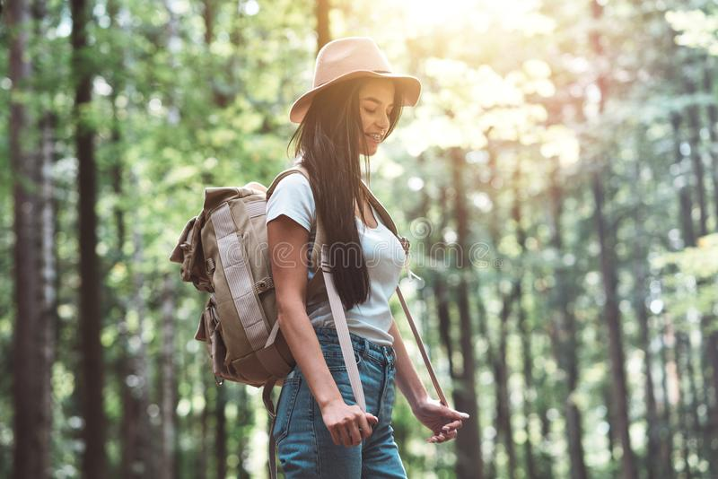 Smiling and happy hipster girl with backpack and hat walking in forest royalty free stock images