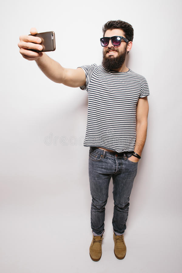 Smiling happy hipster man in sun glasses with beard taking selfie with mobile phone. royalty free stock photography