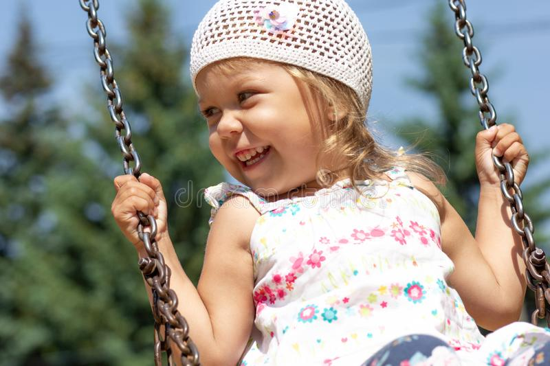 Smiling happy little girl swinging in summer park royalty free stock photography