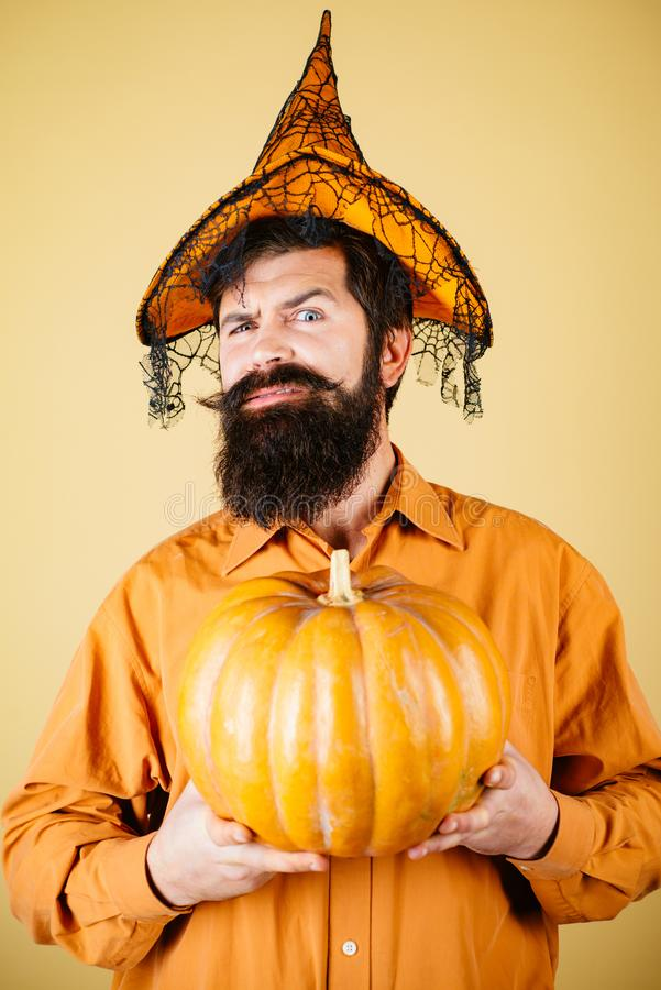 Smiling happy man with pumpkin. Devil man. Thanksgiving day cooking. Young man with witch hat ready to Halloween party. Halloween Man posing with pumpkins stock photo