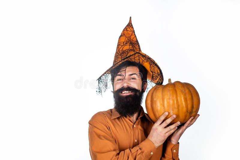 Smiling happy man with pumpkin. Halloween beaded man hold pumpkin - portrait. Devil man. Happy Halloween Weekends. The. Crazy joker face royalty free stock photo