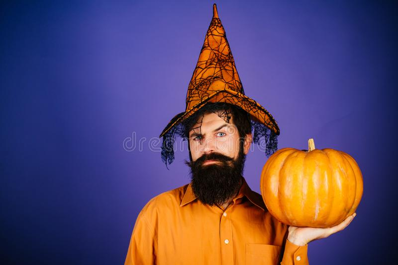Smiling happy man with pumpkin. Halloween Man posing with pumpkins. Celebrating happy Thanksgiving day. Happy Halloween. Thanksgiving day cooking stock image