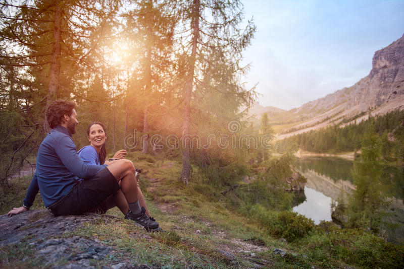 Smiling happy man and woman couple enjoy lake panorama view with sun flare light. Group of friends people summer stock photos