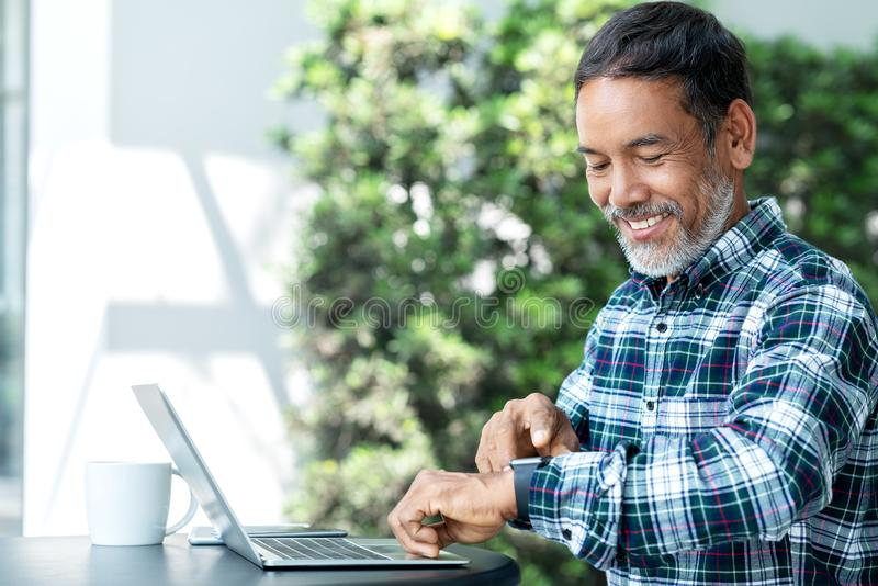 Smiling happy mature asian man with white stylish short beard using digital smartwatch and touching screen at coffee shop outdoor. Old indian or hispanic man royalty free stock photo