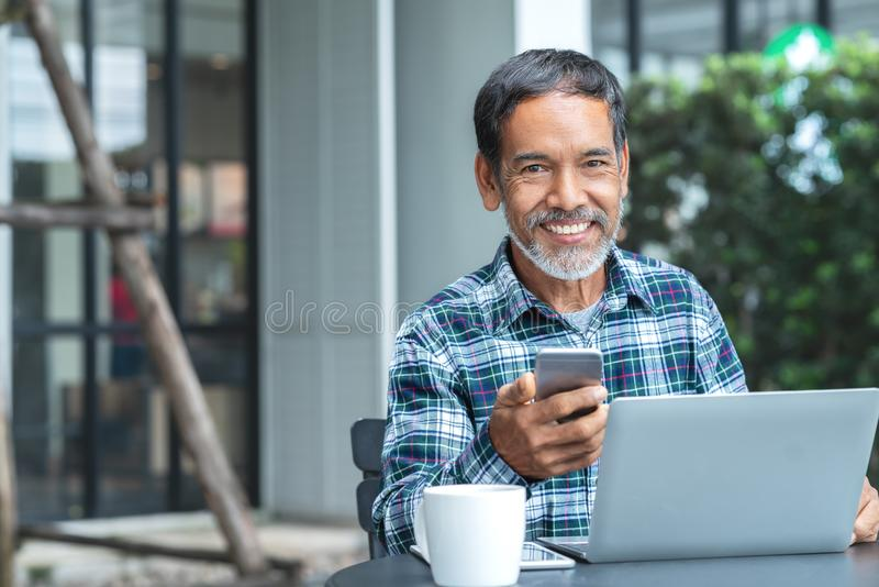 Smiling happy mature asian man with white stylish short beard using smartphone gadget serving internet at coffee shop cafe outdoor. Old indian or hispanic man royalty free stock photography